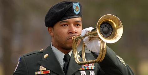 An Army bugler plays taps during military burial services in Cherry Hill, N.J.