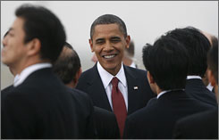 President Obama is greeted by a welcome party during his arrival at Haneda Airport in Tokyo on Friday. This is the beginning of a four-nation Asia trip, his first to the region as president.