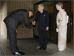 President Obama bows as he is greeted by Japanese Emperor Akihito and Empress Michiko as he arrives at the Imperial Palace in Tokyo on Saturday.