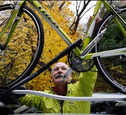Cycle of addiction: Steve Ballou loads his bike atop his car at his home in Sherborn, Mass. Ballou had resumed smoking after a smoke-free decade when he enrolled in a trial for a nicotine vaccine. He says cigarettes no longer taste good.