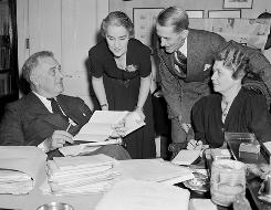 President Franklin D. Roosevelt works on a speech in the office of his Hyde Park, N.Y., estate with, from right, secretaries Grace Tully, Marvin McIntyre, and Marguerite Lehand.