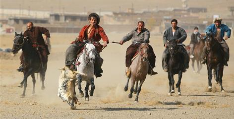 Afghan players on horseback fight for control of a carcass during a game on November 6 in Kabul, Afghanistan.