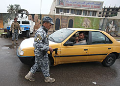 An Iraqi policeman uses a scanner to inspect a taxi at checkpoint in central Baghdad on Tuesday.  Violence has dropped sharply in Iraq over the past year, but politicians and security officials have warned in recent weeks of a possible spike in violence in the run-up to the national polls as insurgents look to undermine the government and destabilize the country.
