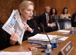 Sen. Kirsten Gillibrand, D-N.Y., holds up the Nov. 17 edition of USA TODAY while questioning Agriculture Secretary Tom Vilsack during a Senate hearing on food safety.