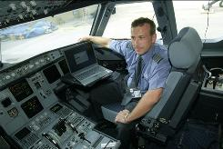 JetBlue Capt. Carmen Ragonese uses a laptop for flight planning in the cockpit of an Airbus A-320. Pilots say the computers enhance safety by giving crews more current information.