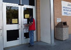 A customer peers through the door of a closed Department of Motor Vehicles branch in Corte Madera, Calif., in July.