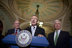 Senate Majority Leader Harry Reid, D-Nev., speaks Saturday after the U.S. Senate voted to begin debate on legislation for a broad health care overhaul, as Sens. Chris Dodd, D-Conn., right, and Tom Harkin, D-Iowa, left, look on.