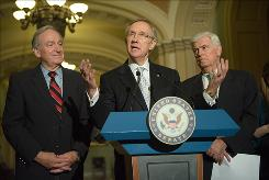 Senate Majority Leader Harry Reid, center, with Sen. Chris Dodd, right, and Sen. Tom Harkin of Iowa, speaks to reporters after Saturday's Senate vote to formally launch debate on a proposed overhaul of the nation's health care system.