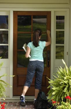 A college student goes door-to-door selling education products in Birmingham, Ala. Communities are increasingly enacting ordinances across the USA that require background checks for people seeking donations or sellng goods.