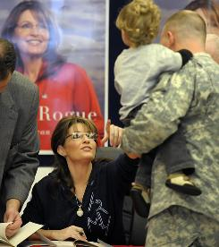 "Sarah Palin talks to a soldier and his son while signing her memoir ""Going Rogue"" at the North Post Exchange Monday in Fort Bragg, N.C."