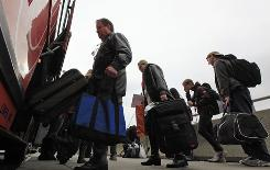 People load luggage onto a bus Tuesday in Philadelphia. Congestion in urban areas begins early on the Wednesday before Thanksgiving.