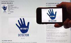 A man holds up an iPhone against an iTunes screen as both show H1N1 Detector, a new application intended to help people better protect themselves against swine flu.