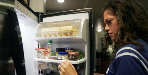 Jacki Seaman, 29, puts away groceries at her apartment in Phoenix. The bad economy has forced Seaman and her husband to cut back on food shopping for their Thanksgiving dinner.