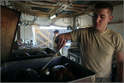 Spc. Seth Breesawitz of Springfield, Mo. uses a ladle to baste his turkeys as he prepares Thanksgiving dinner for the troops in the town of Baraki Barak district, Logar province, Afghanistan on Thursday.