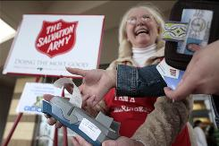 Salvation Army bell-ringer Fran Lephart assists a contributor with a credit card reader in Fredericksburg, Va.