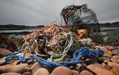 A washed-up lobster trap and tangled line sit on a beach in Biddeford, Maine. Fishermen have been losing and discarding nets and traps for as long as they've plied the world's seas.