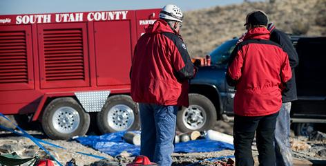 Rescue workers gather at the Nutty Putty Cave in Elberta, Utah to help rescue a man stuck deep in the cave on Wednesday. The recovery effort was on hold Thursday as officials tried to determine how best to proceed.