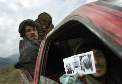 Afghan fighters near Tora Bora hold up a leaflet that advertises a reward for top al-Qaeda officials, such as Osama bin Laden, in 2001. A new Senate report concludes bin Laden was within U.S. reach at that time.