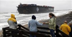 A barge is beached after breaking free from a tugboat Nov. 13 as remnants of Tropical Storm Ida move through the Virginia Beach area.