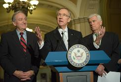 Senate Majority Leader Harry Reid, center, speaks to the press with Senator Chris Dodd, right, and Senator Tom Harkin after the Senate voted to formally launch debate on historic legislation to enact a health care overhaul.