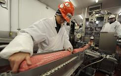 Keith Carrillo checks 10-pound tubes of packaged ground beef on the line at Beef Packers in Fresno. In August, Beef Packers recalled 825,000 pounds of ground beef made in June.