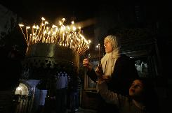 A Palestinian woman and child light candles in the Church of the Nativity, the site revered as the birthplace of Jesus, in the West Bank town of Bethlehem Nov. 29.