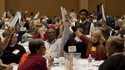 Delegates raise their ballots at the Episcopal Church's annual meeting of the Diocese of Los Angeles in Riverside, Calif., on Friday. The diocese elected its first two female bishops, one of whom is also the second gay bishop in the Church's history.