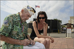 Pearl Harbor survivor Harold B. O'Connor autographs a card for Rebecca Dale, of Melbourne, Australia, as work continues behind them on the new visitor center for the USS Arizona Memorial.
