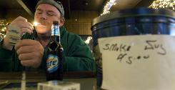 "Joe Wallace of Hammond, Ind., lights a cigarette at Crow Bar in Chicago on Dec. 6. Bar owner Pat Carroll does not enforce the city's smoking ban but encourages donations to a ""smoke jug"" to help offset any fines."