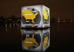 A video projected onto a floating cube in front of a planetarium in Copenhagen shows the level of carbon dioxide emissions by the United States.