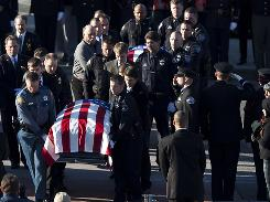 The caskets of Lakewood, Washington police officers Ronald Owens, front, and Greg Richards are carried into the Tacoma Dome prior to a public memorial service on Tuesday in Tacoma, Washington.