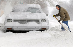 Ken Lee digs a path Tuesday morning to get his car out after 5 inches of snow fell in the in Salina, Kansas area.