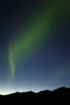 The aurora borealis rises through the Big Dipper constellation high above the Alaska Range in Denali National Park, Alaska.