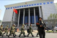 Chinese paramilitary police march past the Intermediate People's Court in Urumqi on Sept. 12.