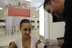 Nurse Marcel Giguere, right, gives an H1N1 shot to Yoanet Ramirez at Airport MD in Miami International Airport over the Thanksgiving holiday. The CDC warns that holiday travel can spread the flu.