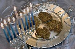 Oven-crisped potato latkes sit on a plate next to a menorah for a Hanukkah celebration.