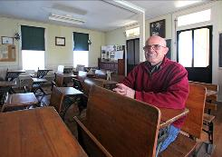 George House, 78, sits at a desk in a schoolhouse in Lancaster, Iowa. He attended the old country school and later taught there.