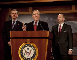 Senate Minority Leader Mitch McConnell speaks about the 1.1 trillion government spending bill at a news conference on Capitol Hill as Sens. Judd Gregg and George LeMieux stand by on Saturday.