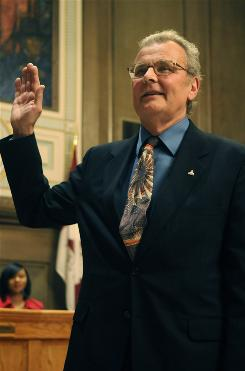 "Cecil Bothwell takes the oath of office for the Asheville City Council Dec. 8. His opponents say the admitted athiest can't serve because North Carolina law disqualifies candidates who ""deny the being of Almighty God."""
