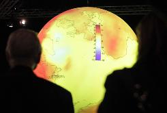 Delegates look at a high-tech display about the warming of the world's oceans at the U.S. booth during the climate summit in Copenhagen on Dec. 8.