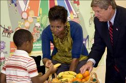 First lady Michelle Obama hands out fruit to students with Agriculture Secretary Tom Vilsack at Hollin Meadows Science and Math Focus School in Alexandria, Va., on Nov. 18.