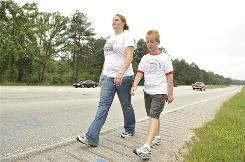 Zach Bonner walks down Highway 78 in Monroe, Ga., with his sister Kelley, 21, in May. The 11-year-old founded Little Red Wagon Foundation and walked 1,225 miles from his home in Tampa to Washington, D.C., to raise awareness and funds for homeless children.