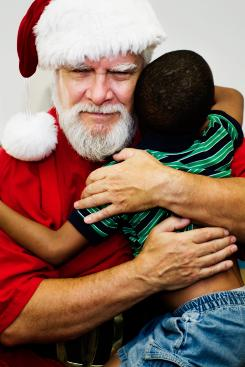 Santa Ernie, a volunteer specially trained by Santa-America, hugs a Hurricane Katrina victim.