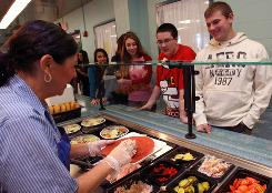 Christine Martin prepares a wrap for sophmore Anthony Centone, 16 right, during lunch at Lakeland High School. The school district operates its own cafeteria, and has gone years without a single major violation, according to health department records.