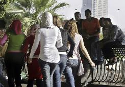 Egyptian boys watch passing girls at the Nile bank in Cairo. Sexual harassment of women in Arab streets, schools and work places may be driving more and more women to cover up.