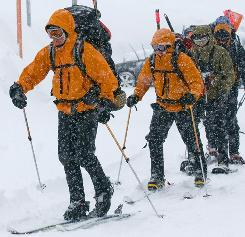 Members of the 304th Rescue Squadron leave the parking lot at Timberline on their way up the slopes of Mount Hood on Tuesday to make an assessment of the avalanche danger and to practice their avalanche training as they wait for better weather to continue the search for two missing climbers.
