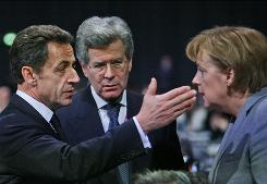 Germany's Chancellor Angela Merkel, right, talks with French President Nicolas Sarkozy, left, Thursday during the U.N. summit on climate change in Copenhagen.