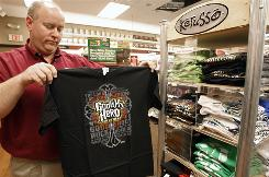"Matt Jaggers, the manager of the Lifeway Christian Store in Nashville, Tenn., holds up a shirt which has the phrase ""God is my hero"" in the likeness of the logo for the popular video game ""Guitar Hero."" The design is one of many used by the Kerusso company that parodies logos of popular products and television shows."