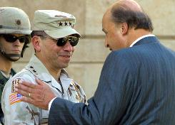 Lt. Gen. Ricardo Sanchez is greeted by John Negroponte, then-U.S. ambassador to Iraq, at the U.S. Embassy in Baghdad in June 2004.