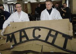 Police officers display  a part of the retrieved inscription from the Auschwitz Birkenau entrance, during a news conference in Krakow, Poland, on Tuesday. The infamous inscription &quot;Arbeit Macht Frei&quot; from the former Nazi death camp Auschwitz Birkenau was stolen Dec. 18, 2009 and retrieved by the Polish police three days later. 